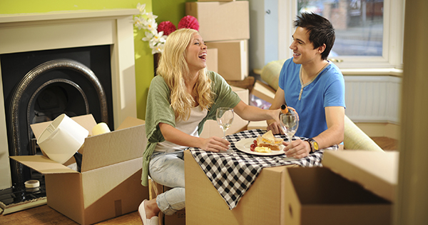 Young couple enjoy a meal on a cardboard box while in the middle of unpacking.